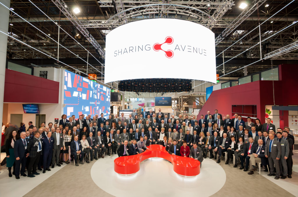 In an exhibition hall hundreds of people in suits stand lined up for a photo; copyright: Arneg