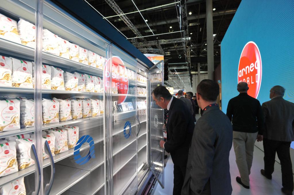 People stand in front of a glass shelf in which pasta packs are placed.