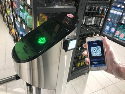 One hand holds a smartphone with a barcode on it against a stele in the supermarket