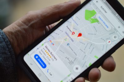 Hand holding smartphone with Google Maps and the location of a butcher's shop on display; copyright: henry perks/Unsplash