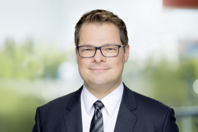 Man with glasses in a suit smiles into the camera; copyright: dm-drogerie markt GmbH