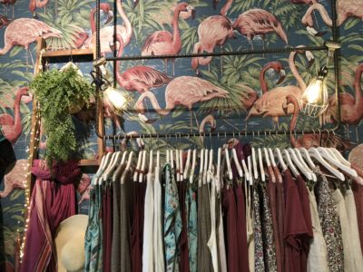 Clothes rack in front of a wall with pink flamingos