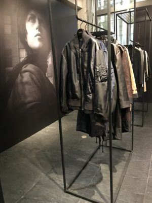 A coat rack with clothes in a modern gallery