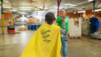 "A boy stands facing a woman with his back to the camera, wearing a yellow cape that reads ""Zero Hunger, Zero Waste, Kroger"""
