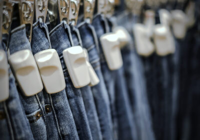 Several jeans chipped with RFID tag on clothes rail; copyright: PantherMedia / Myimagine