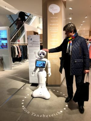 A customer in a fashion store strokes a white little robot's head; copyright: Humanizing Technologies GmbH