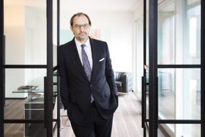 A man in a suit is standing in an office door