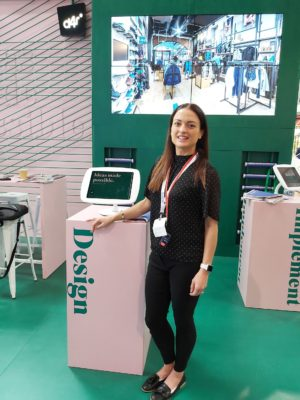 A young woman stands at an exhibitor stand