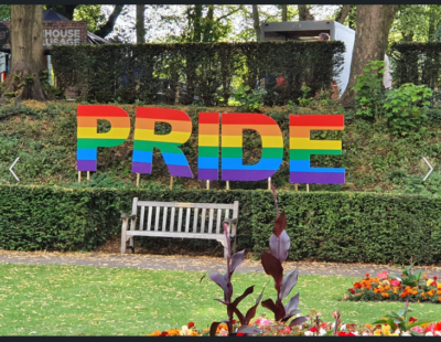 """The word """"Pride"""" in large rainbow-colored letters in a park"""