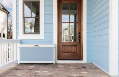 Light blue house with brown wooden door and box in front of the door; copyright: Walmart