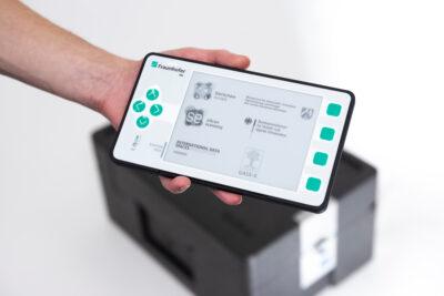 Device in Smartphone-Format vor Liefer-Box; copyright: Fraunhofer IML