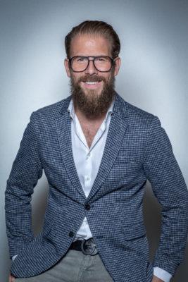 man in sacko and with glasses smiles into the camera; copyright: Martin Kielmann