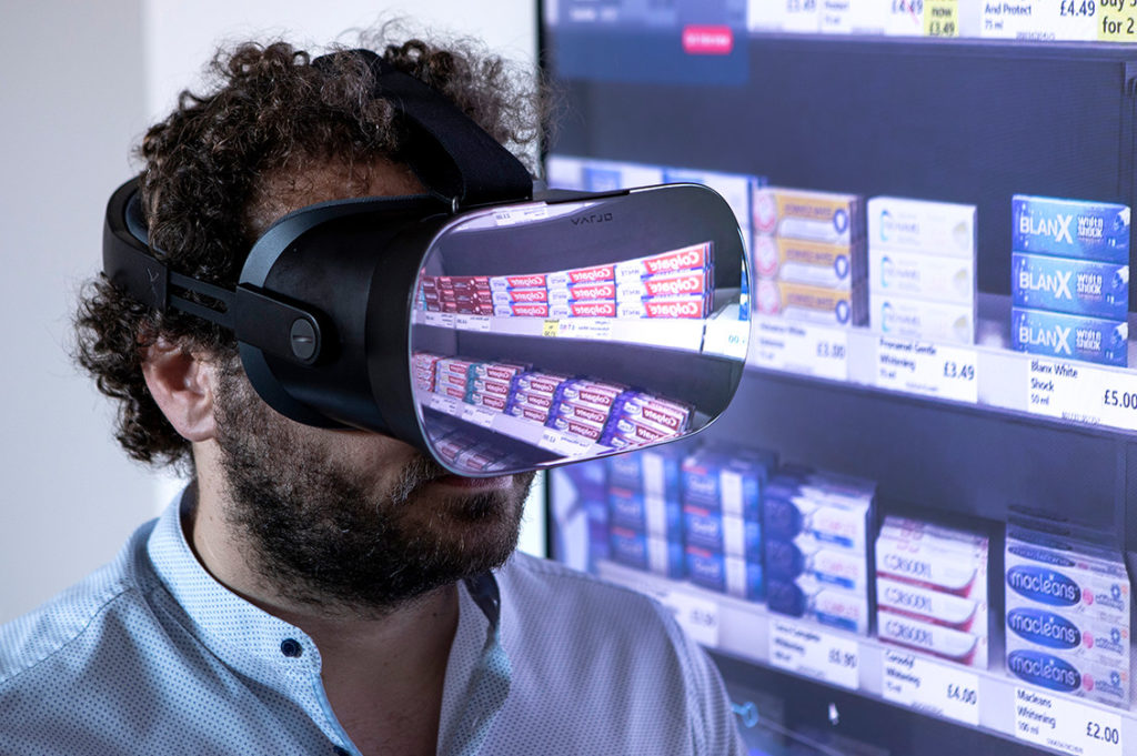 man infront of a shelf wearing vr glasses