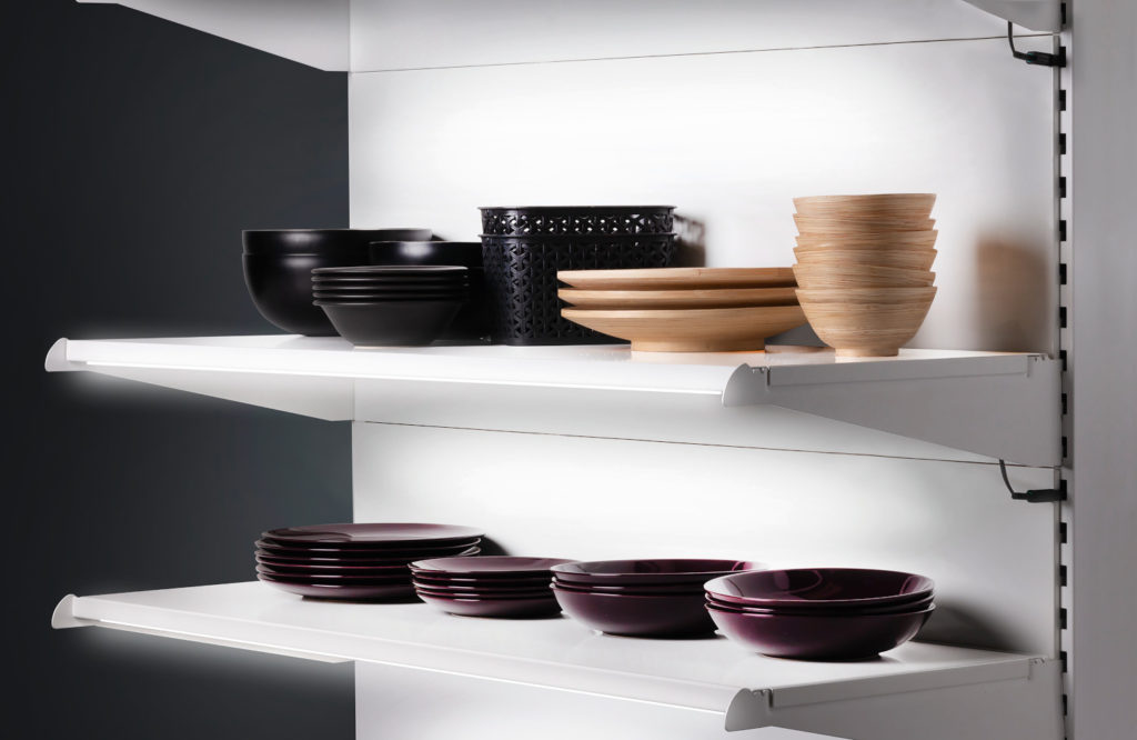 A white wall shelf with three shelves and plates and dishes on them