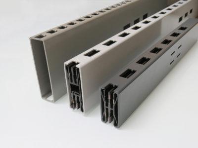 Three grey shelf conductor rails lying side by side