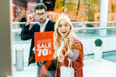 Surprised shoppers in front of shop window with sale sign