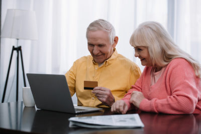 Two seniors - man and woman - sitting in front of their laptop and shopping online