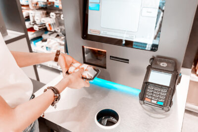 A person holds a package of sushi in front of the scanner of a self-service terminal