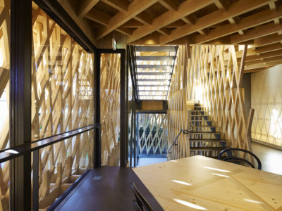 A building with a wooden grid as facade through which the sun shines; view from inside