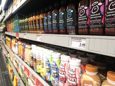 Supermarket shelf, diagonally photographed with juices and smoothies