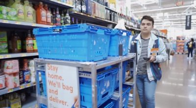 A man in a supermarket pushes a trolley with blue baskets through the shelves