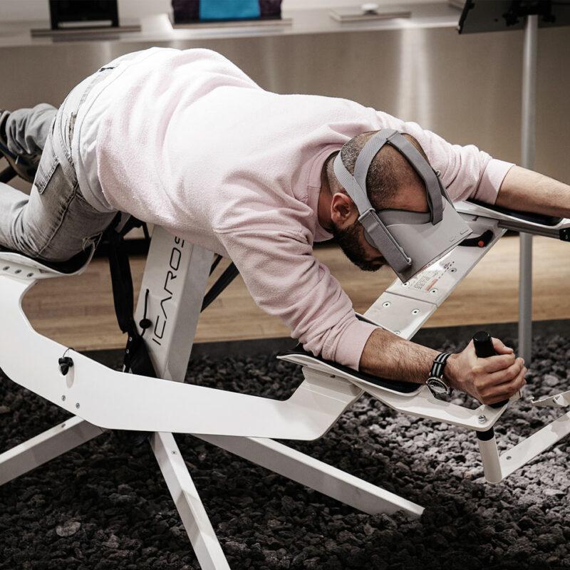 Mann mit VR Brille liegt in Flugsimulator. Innovative Premium-Produkte laden bei Vaund in Hannover zum Ausprobieren ein. © Realtale