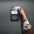 Eine Hand, die eine giro-KArte vor ein Bezahl-Terminal hält