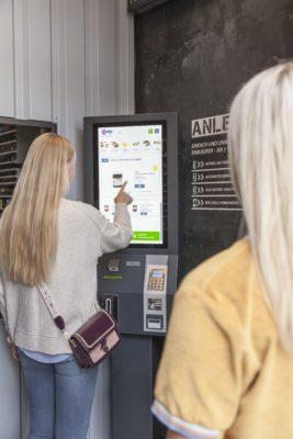 Frau steht vor Touchscreen und wählt Lebensmittel aus; copyright:Wanzl GmbH & Co.KGaA.