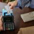 Hand die Bankkarte an Bezahlterminal hält; copyright: girocard