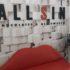 Ein rotes Sofa in Form eines Mundes vor einer Wand aus weißen Blöcken