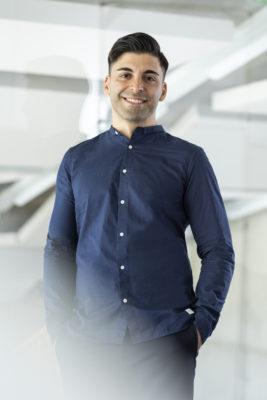 Portrait eines jungen lächelnden Mannes in einem Blauen Hemd