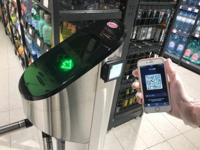 Eine Hand hält ein Smartphone mit Barcode drauf an eine Stele im Supermarkt