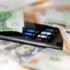 Geldscheine, die über einem Smartphone liegen; copyright:PantherMedia / SlayStorm