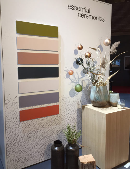 Wall with a colour palette in earth tones with shrub and Christmas tree balls in front; copyright: iXtenso/Pott