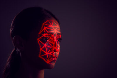 Woman in front of dark background with red laser beams on face; copyright