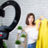 A Chinese woman holding up a piece of clothing towards a camera