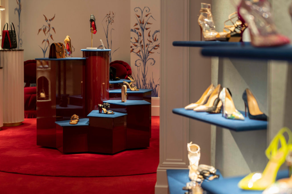 A luxury shoe boutique with blue velvet shoe shelves
