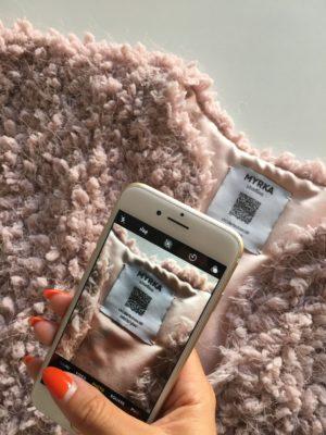 Ein Smartphone scannt ein etikett in einem Kleidungsstück