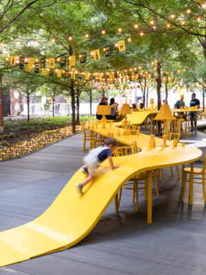 A very long curved yellow table in a city beneath trees with people