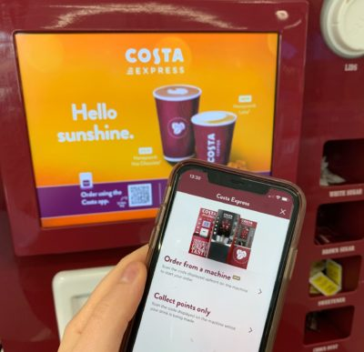 A hand holding a smartphone in front of a coffee vending machine