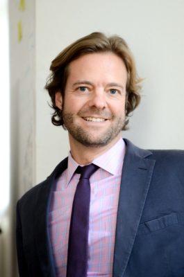 Mann im Anzug und Krawatte lächelt in die Kamera; copyright: IDEE GmbH