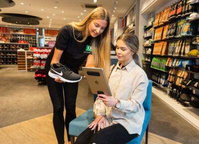 Eine Verkäuferin und eine Kundin im Schuhgeschäft