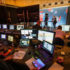 A film recording in a studio with technician, monitors and presenter at the console