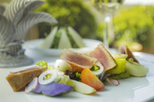Ein schön angerichtetes Gericht auf einem Tisch mit Pflanzen im Hintergrund