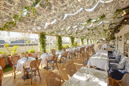 Stühle und Tische eines Restaurants auf einer sonnigen, überdachten Terrasse
