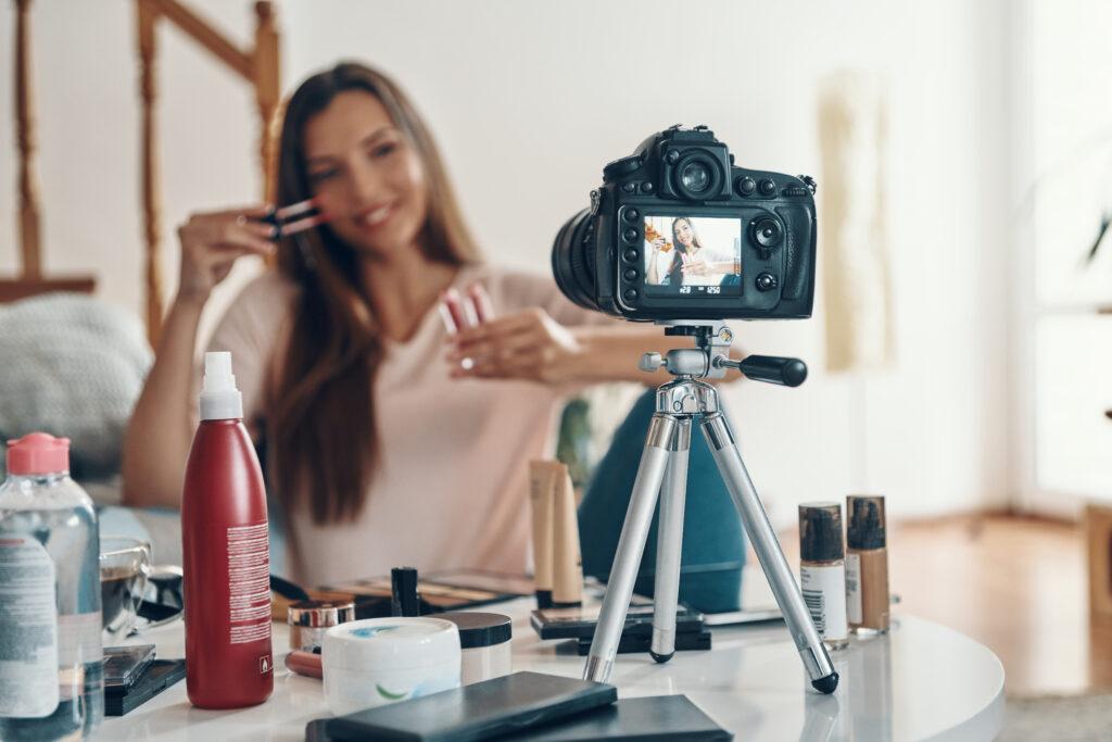 Gut aussehende junge Frau, die Lipgloss aufträgt und lächelt, während sie ein Social-Media-Video macht; xopyright: gstockstudio