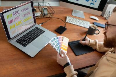 Mann vor Laptop mir Farbproben; copyright: Pressmaster
