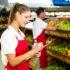 Frau mit roter Schürtze im Supermarkt, die sich auf einer Klemme Notizen macht