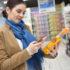 Frau scannt Shampooflasche mit ihrem Smartphone