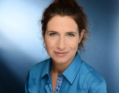 Frau in blauer Bluse und braunem Pferdeschwanz schaut in die Kamera; copyright: Elena Gatti / Azoya